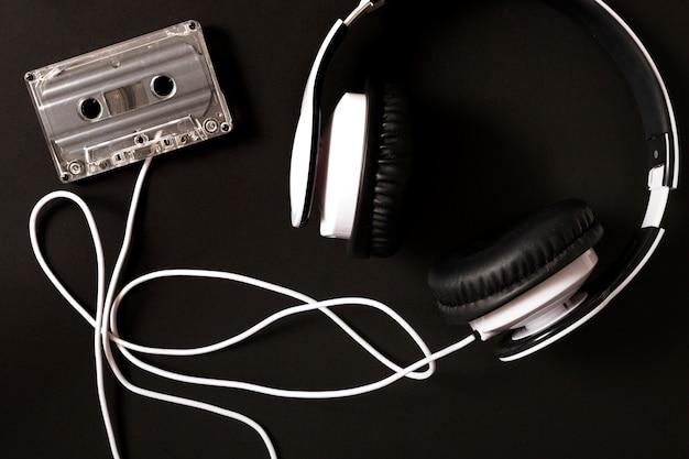 Auriculares conectados a cassette transparente sobre fondo negro