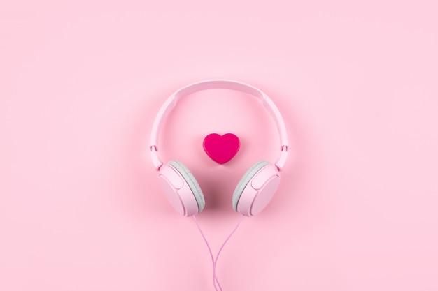 Auriculares y corazón rosados en fondo rosado