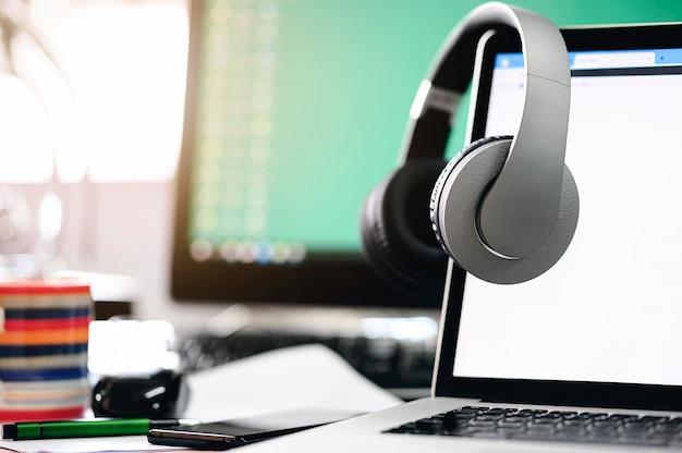 Los auriculares cuelgan del monitor de la computadora portátil con pantalla en blanco.