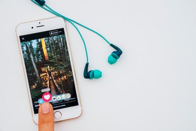 Auriculares y dedo usando facebook en el móvil