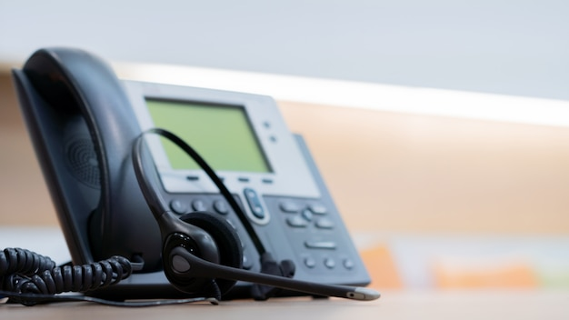 Auriculares con dispositivos telefónicos en el escritorio de la oficina por concepto de soporte de servicio al cliente