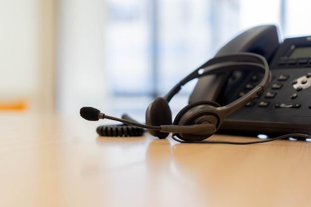 Auriculares con dispositivos telefónicos en el escritorio de oficina para el concepto de soporte de servicio al cliente