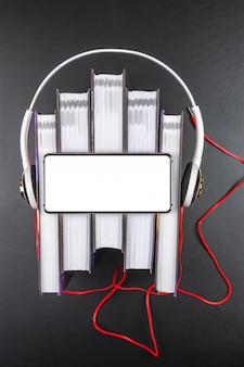Los auriculares están en una pila de libros.