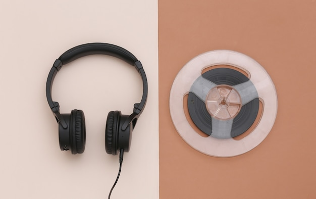 Auriculares estéreo y carrete de audio magnético sobre fondo beige marrón. vista superior