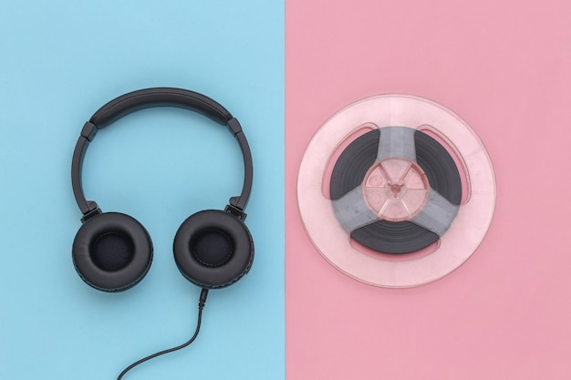 Auriculares estéreo y carrete de audio magnético sobre fondo rosa pastel azul. vista superior