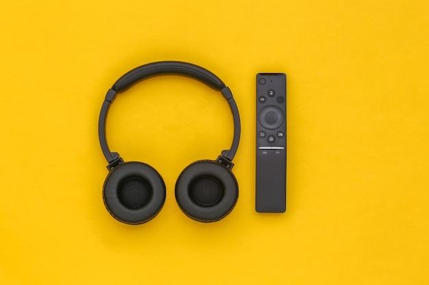 Auriculares estéreo inalámbricos y control remoto de tv sobre fondo amarillo. vista superior