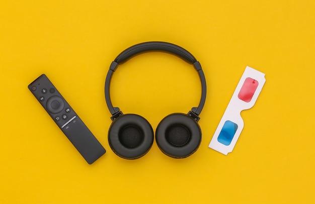 Auriculares estéreo inalámbricos, gafas 3d y control remoto de tv sobre fondo amarillo. vista superior