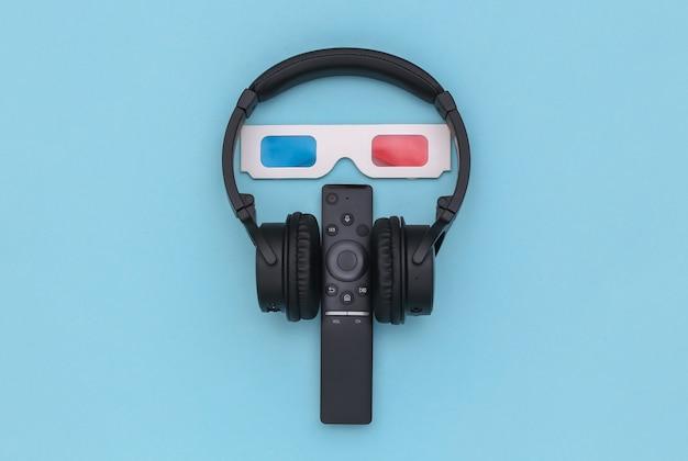 Auriculares estéreo inalámbricos, gafas 3d y control remoto de tv sobre fondo azul. vista superior