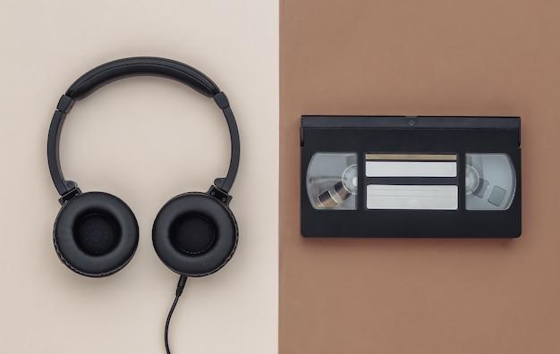 Auriculares estéreo y video cassette sobre fondo beige marrón. vista superior
