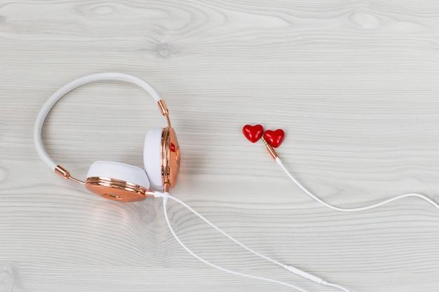 Auriculares femeninos blancos y dos corazones rojos sobre un fondo claro