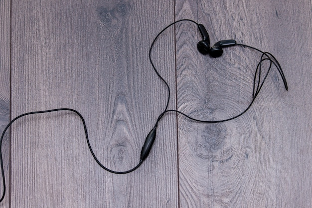 Auriculares en forma o corazón sobre fondo de madera. lay flat, copia espacio.