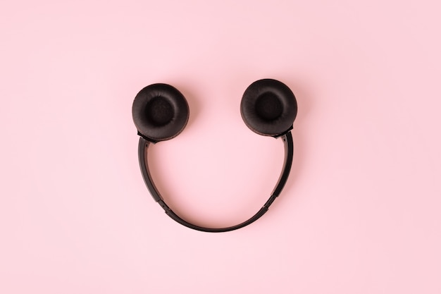 Auriculares en forma de sonrisa sobre fondo rosa, vista superior, concepto de música y sonido