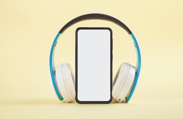 Auriculares inalámbricos blancos y smartphone sobre fondo amarillo.
