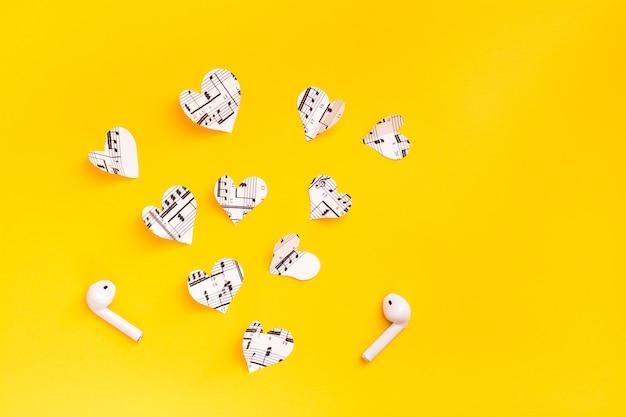 Auriculares inalámbricos y corazones cortados del texto musical sobre una superficie amarilla. amor por la música a través de gadgets.