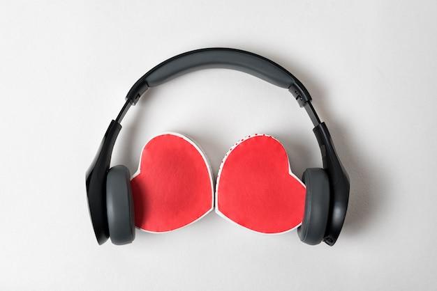Auriculares inalámbricos y dos cajas en forma de corazón. concepto de música de amor fondo blanco, directamente arriba.
