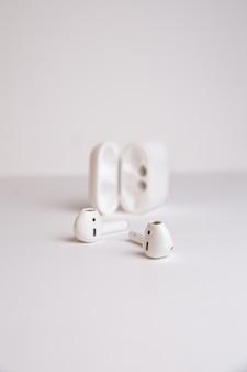 Auriculares inalámbricos con estuche en una pared blanca