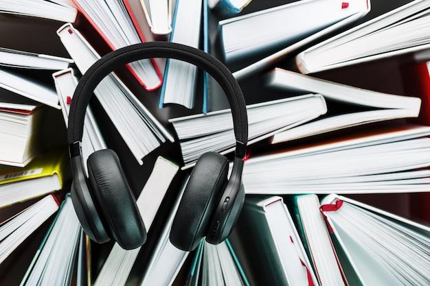 Los auriculares inalámbricos negros se encuentran sobre los libros. el concepto de aprendizaje a través de un audiolibro. para escuchar el libro.