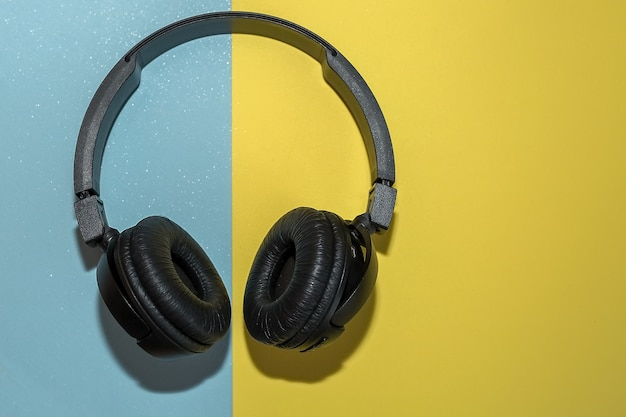Auriculares inalámbricos negros sobre un fondo doble de amarillo y azul.