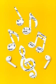 Auriculares inalámbricos y notas musicales cortadas de papel sobre una superficie amarilla. concepto de imitación de música. vista vertical