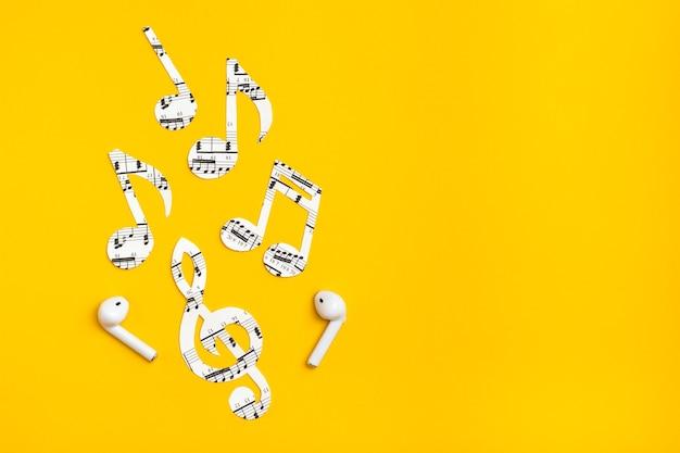 Auriculares inalámbricos y notas musicales cortadas de papel sobre una superficie amarilla. concepto de imitación de música.