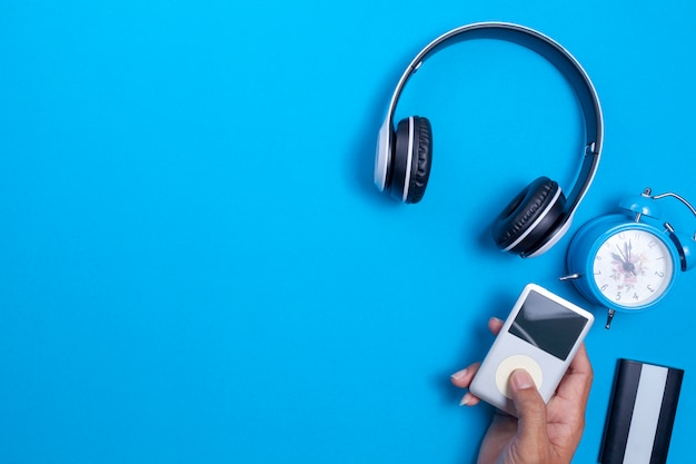 Auriculares inalámbricos y reproductor multimedia, reloj despertador azul sobre fondo de papel azul