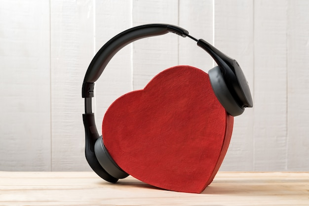 Auriculares inalámbricos de tamaño completo con una caja roja en forma de corazón. concepto de música de amor vista frontal
