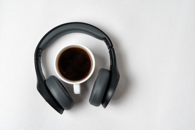 Auriculares inalámbricos de tamaño completo y una taza de café. directamente arriba
