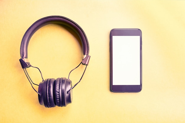 Auriculares inalámbricos y teléfono inteligente maqueta sobre fondo de colores