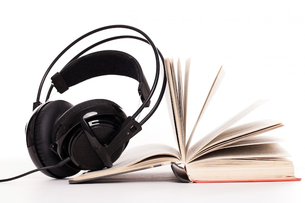 Auriculares y libro sobre un fondo blanco.
