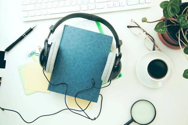 Auriculares, libro y teclado sobre mesa