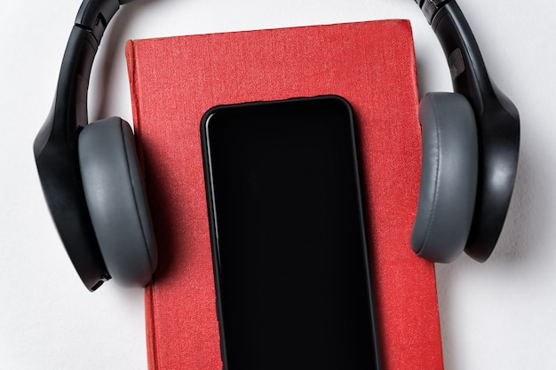 Auriculares, libro y teléfono celular sobre fondo blanco. concepto de libro o audiolibro. copiar espacio, cerrar