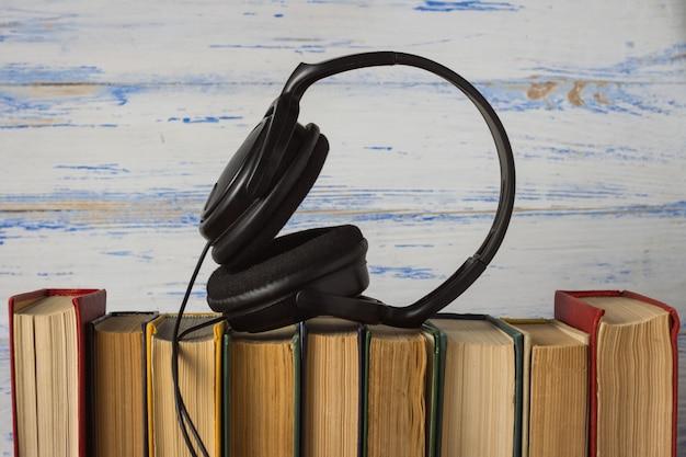 Auriculares en libros plegados sobre el fondo blanco de madera