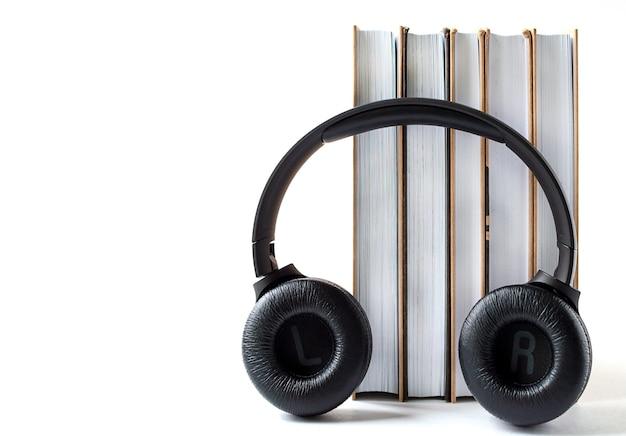 Auriculares y libros sobre un fondo blanco. concepto de audiolibro con espacio de copia.