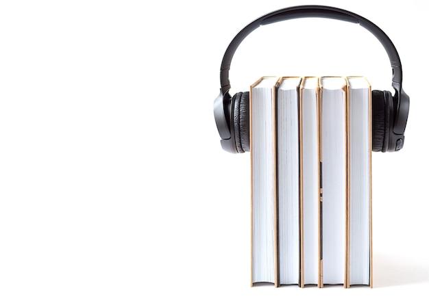 Auriculares y libros sobre un fondo blanco. concepto de audiolibro.