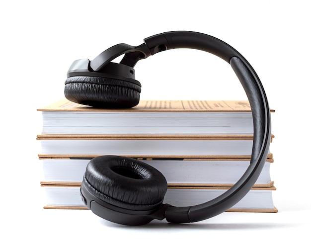 Auriculares y libros sobre un fondo blanco.