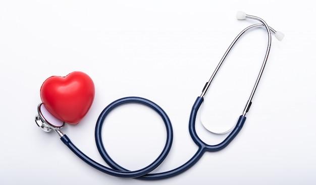 Auriculares médicos, estetoscopio con corazón rojo sobre fondo blanco.