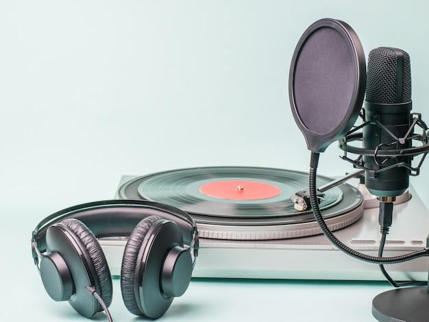 Auriculares, micrófono y tocadiscos de vinilo sobre una superficie liviana