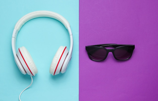 Auriculares modernos con gafas de sol sobre fondo de color. concepto de música creativa. estilo retro.