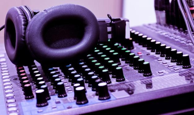 Auriculares negros en el mezclador de la placa de sonido de la consola
