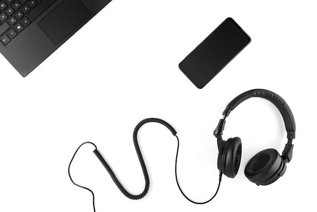 Auriculares negros, smartphone y portátil sobre un fondo blanco.