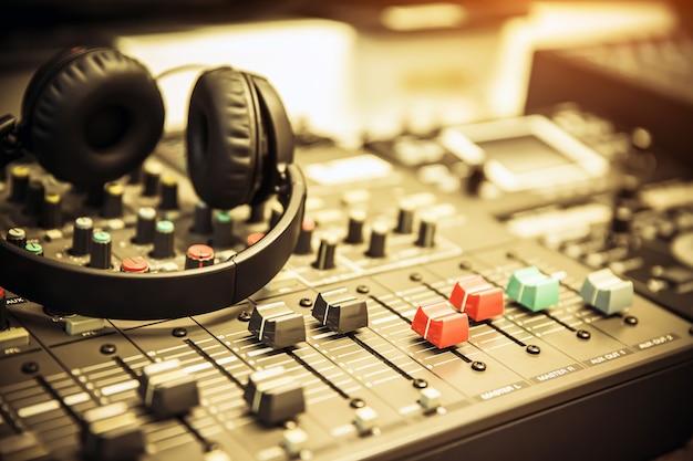 Auriculares de primer plano con mezclador de audio en estudio