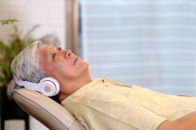 Los auriculares que escuchan del hombre asiático mayor whlie que ponen en el sofá en la sala de estar casera con felicidad