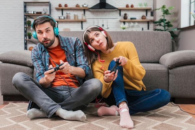 Auriculares que llevan de los pares jovenes que se sientan en piso cerca del sofá que juega el videojuego