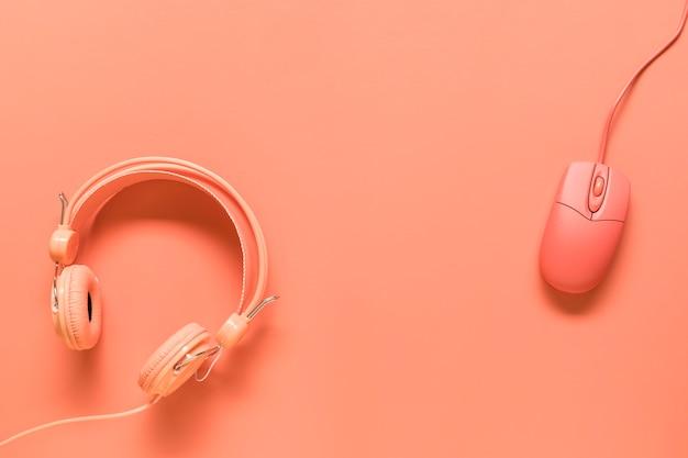 Auriculares y ratón sobre fondo naranja