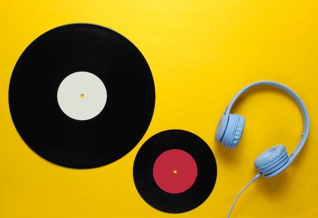Auriculares, registros lp sobre fondo amarillo