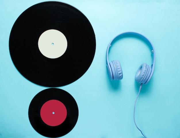 Auriculares, registros lp sobre fondo azul.
