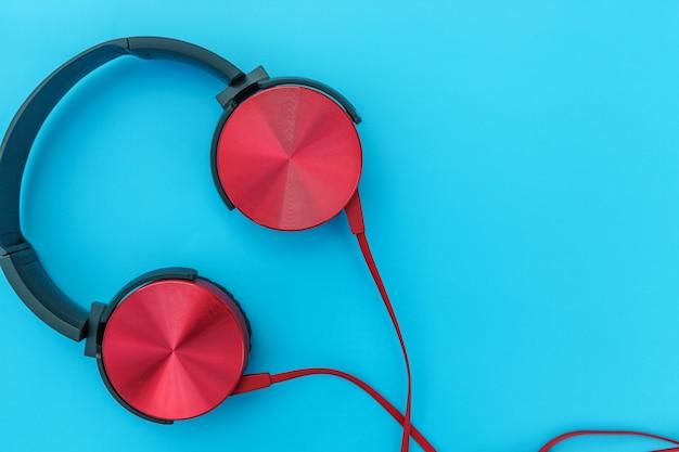 Auriculares rojos con cable aislado sobre fondo azul pastel colorido