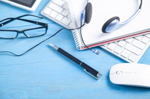 Auriculares de servicio al cliente, teclado de computadora y objetos comerciales en el fondo azul.