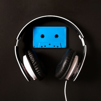 Auriculares sobre la cinta de cassette azul sobre fondo negro