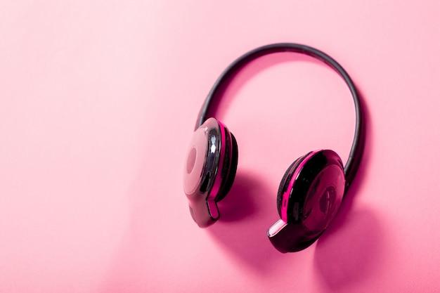 Auriculares sobre fondo rosa